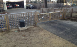 Wooden cantilever gate installed on sloped driveway
